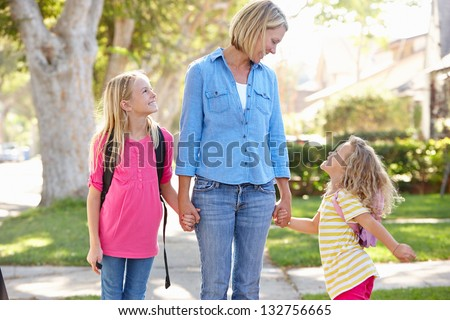 Mother And Daughters Walking To School On Suburban Street - stock photo