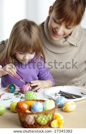 mother and daugther painting easter eggs together