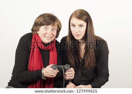 mother and daugthter are playing a video game, holding the controller - stock photo