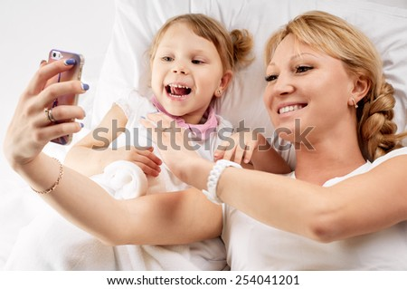 Mother and dauhter taking photo with her smart-phone camera in the bed - stock photo