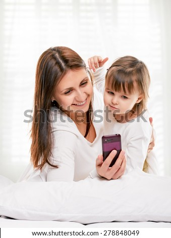 Mother and dauhter taking photo with her smart-phone camera in the bed on light window background - stock photo