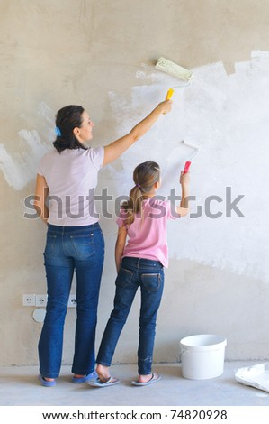 Mother and douther painting a wall with roller - stock photo