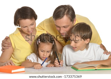Mother and father doing homework with their kids - stock photo
