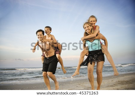 Mother and father give their children piggy back rides at the beach. Horizontal shot.