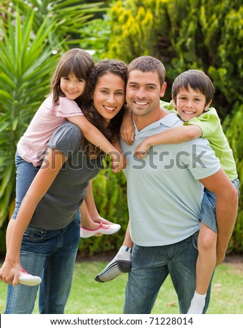 Mother and father giving children a piggyback