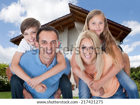 Mother And Father Giving Children A Piggyback In Front Of House - stock photo