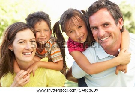 Mother And Father Giving Children Piggy Back - stock photo