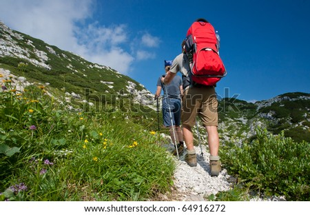 mother and father hike with baby in baby carrier, julijan alps, slovenia - stock photo