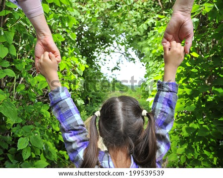 mother and father holding hands his daughter - stock photo
