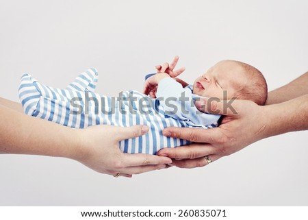 Mother and father holding newborn baby - stock photo