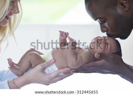 Mother and Father holding their new born baby. The mother is smiling and the father is kissing the baby's head. - stock photo
