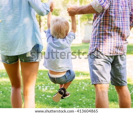 Mother and father holding their son in the air in the summer garden.