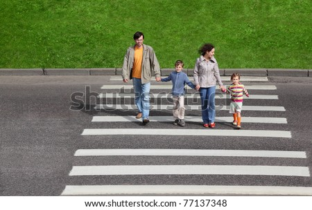 mother and father holds hand of little daughter and son and crossing road, green fence and grass - stock photo