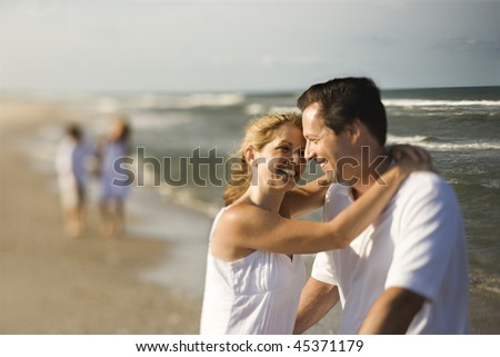 Mother and father hug on a beach with children playing in the distance. Horizontal shot. - stock photo