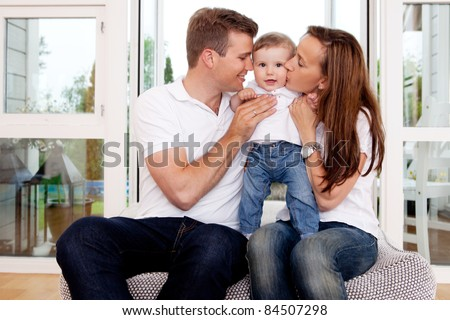 Mother and father hugging and kissing son in home interior