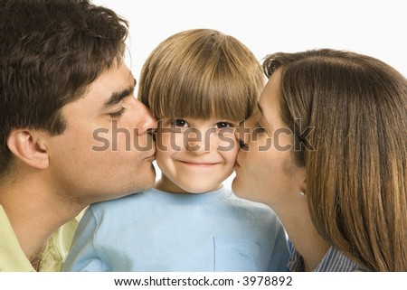 Mother and father kissing son on opposite cheeks. - stock photo