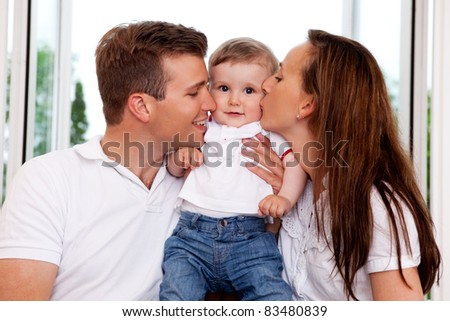Mother and Father kissing their toddler son on the cheek