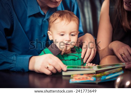 mother and father reading book to son - stock photo