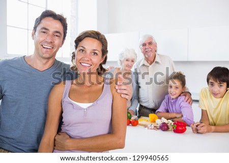 Mother and father standing by kitchen counter with family behind them - stock photo
