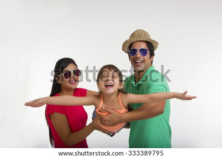 Mother and father swinging daughter - stock photo