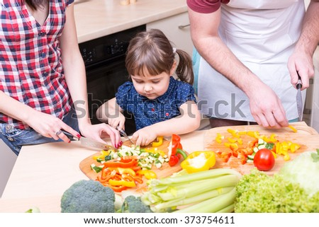 mother and father teaching girl how to cook - stock photo