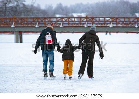 Mother and father teaching kid to skate on the rink in winter. Skating involves any sports or recreational activity which consists of traveling on surfaces or on ice using skates. - stock photo