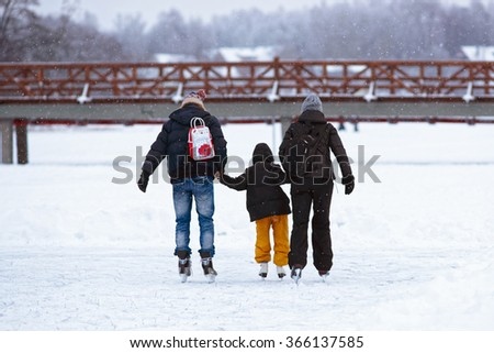 Mother and father teaching their kid to skate on the rink in winter. Skating involves any sports or recreational activity which consists of traveling on surfaces or on ice using skates. - stock photo
