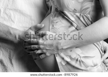Mother and Father to be with hands on belly - stock photo