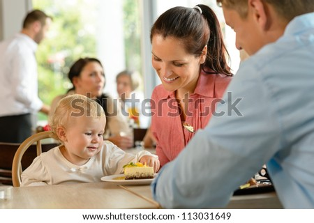 Mother and father with child eating cake woman man cafe - stock photo