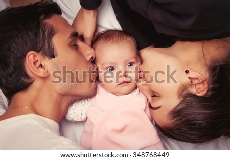Mother and father with little baby in a bed  - stock photo