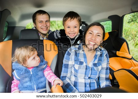 Mother and father worried about her children's safety in a car. Son and daughter near to mom Babes sitting inside modern auto. Parent look at camera. The idea of safe traffic
