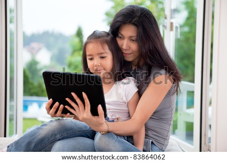 Mother and girl holding E-book reader at home - stock photo