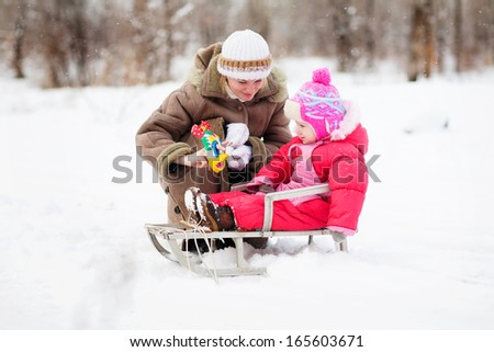 mother and girl playing in snow - stock photo