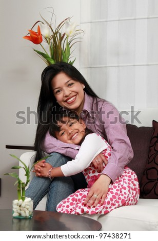 mother and girl smiling in the living room - stock photo
