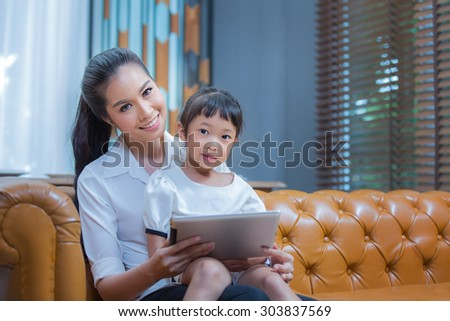 Mother and girl with tablet computer in the living room - stock photo