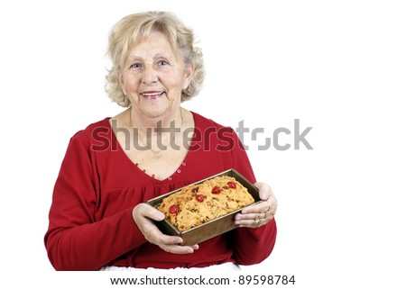 Mother and grand-mother welcoming her family with a smile and a freshly baked home made fruit cake. - stock photo