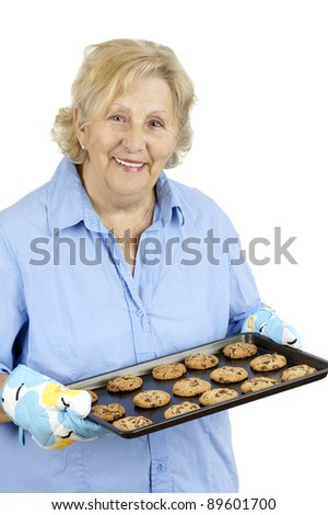 Mother and grand-mother welcoming her family with a smile and freshly baked home made chocolate cookies. - stock photo