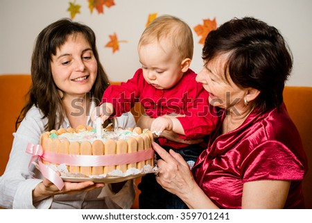 Mother and grandmother with baby celebrating first birthday - child damaging cake - stock photo