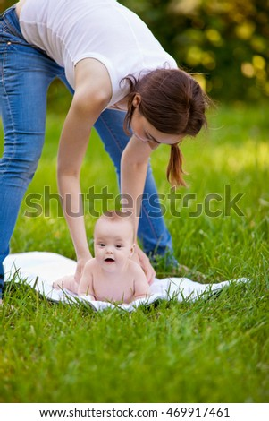 Mother and happy baby doing exercise routine on green grass outdoors