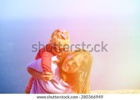 mother and happy little daughter play on summer sky - stock photo