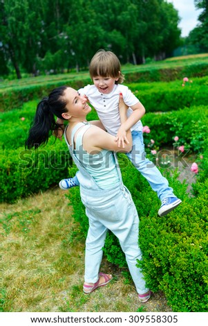 Mother and happy son playing in summer park.  - stock photo
