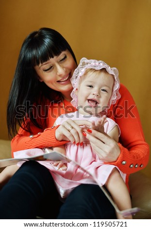 Mother and her baby girl playing at home - stock photo