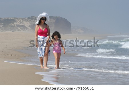 mother and her baby in the beach near the water
