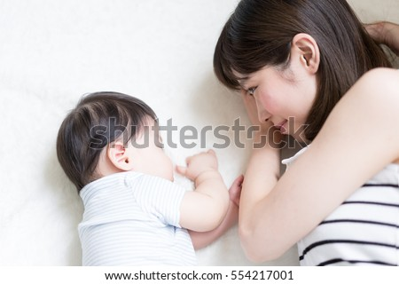 mother and her baby lying on a bed