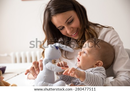 Mother and her baby playing with Bunny toy. - stock photo