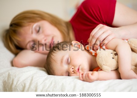 mother and her baby sleeping together - stock photo