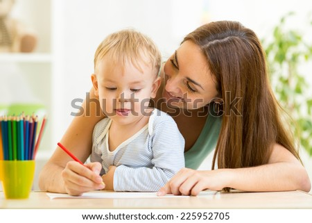 mother and her child boy pencil together - stock photo