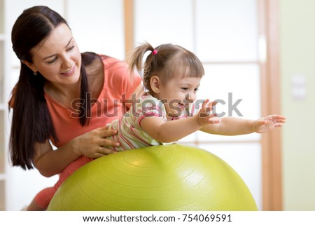 Mother and her child daughter playing with fitness ball