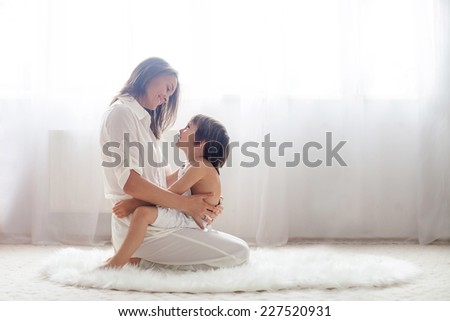 Mother and her child, embracing with tenderness and care - stock photo