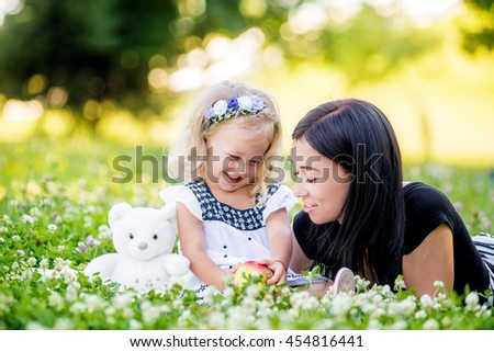 Mother and her child enjoy the early spring, eating apple, happy.
